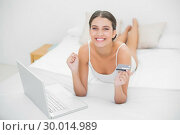 Victorious young brown haired model in white pajamas shopping online with her laptop. Стоковое фото, агентство Wavebreak Media / Фотобанк Лори