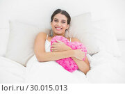 Купить «Content young brown haired model in white pajamas cuddling a heart shaped pillow», фото № 30015013, снято 25 июня 2013 г. (c) Wavebreak Media / Фотобанк Лори