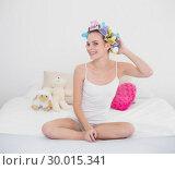 Купить «Content natural brown haired woman fixing her hair curlers», фото № 30015341, снято 26 июня 2013 г. (c) Wavebreak Media / Фотобанк Лори