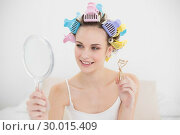 Купить «Beautiful natural brown haired woman in hair curlers looking herself in a mirror», фото № 30015409, снято 26 июня 2013 г. (c) Wavebreak Media / Фотобанк Лори