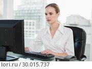 Купить «Serious businesswoman sitting at desk », фото № 30015737, снято 26 июня 2013 г. (c) Wavebreak Media / Фотобанк Лори