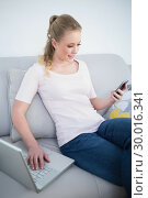 Купить «Casual smiling blonde using smartphone and laptop», фото № 30016341, снято 2 июля 2013 г. (c) Wavebreak Media / Фотобанк Лори