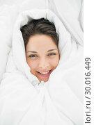 Купить «Smiling casual brunette wrapped up in her duvet», фото № 30016449, снято 5 июля 2013 г. (c) Wavebreak Media / Фотобанк Лори