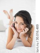 Купить «Smiling casual brunette in white pajamas calling with her mobile phone», фото № 30016489, снято 5 июля 2013 г. (c) Wavebreak Media / Фотобанк Лори