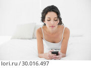 Relaxed casual brunette in white pajamas texting with a mobile phone. Стоковое фото, агентство Wavebreak Media / Фотобанк Лори