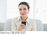 Dreamy stylish brunette businesswoman using her mobile phone. Стоковое фото, агентство Wavebreak Media / Фотобанк Лори