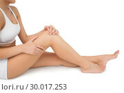 Купить «Slim woman sitting on floor touching her injured knee», фото № 30017253, снято 31 июля 2013 г. (c) Wavebreak Media / Фотобанк Лори