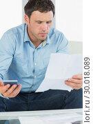 Купить «Worried casual man holding calculator paying bills looking at document», фото № 30018089, снято 24 июля 2013 г. (c) Wavebreak Media / Фотобанк Лори