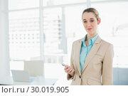 Купить «Pretty chic businesswoman holding her smartphone smiling at camera», фото № 30019905, снято 17 июля 2013 г. (c) Wavebreak Media / Фотобанк Лори