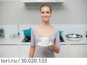 Купить «Lucky gorgeous model looking at camera holding mug», фото № 30020133, снято 30 мая 2013 г. (c) Wavebreak Media / Фотобанк Лори