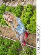 Купить «Young woman making use of a rake in her garden», фото № 30020517, снято 4 июля 2013 г. (c) Wavebreak Media / Фотобанк Лори