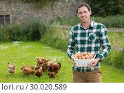 Купить «Proud young man holding a basket filled with eggs», фото № 30020589, снято 4 июля 2013 г. (c) Wavebreak Media / Фотобанк Лори