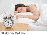Купить «Woman in bed with alarm clock in foreground», фото № 30022789, снято 16 июля 2013 г. (c) Wavebreak Media / Фотобанк Лори