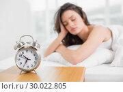 Купить «Sleepy woman with alarm clock in foreground», фото № 30022805, снято 16 июля 2013 г. (c) Wavebreak Media / Фотобанк Лори
