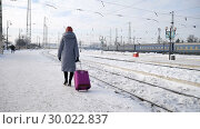 Купить «Back view of young woman in blue coat waiting for a train standing at the railway station with purple luggage suitcase early in the morning during winter time», видеоролик № 30022837, снято 13 февраля 2019 г. (c) Ольга Балынская / Фотобанк Лори