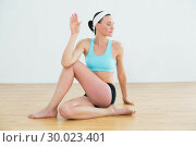 Купить «Woman doing the spine twisting pose at fitness studio», фото № 30023401, снято 18 июля 2013 г. (c) Wavebreak Media / Фотобанк Лори