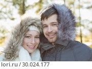 Купить «Smiling young couple in fur hood jackets in the woods», фото № 30024177, снято 22 августа 2013 г. (c) Wavebreak Media / Фотобанк Лори