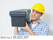 Smiling handyman in yellow hard hat carrying toolbox. Стоковое фото, агентство Wavebreak Media / Фотобанк Лори