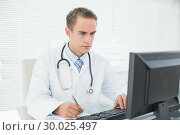 Doctor writing a note while using computer at medical office. Стоковое фото, агентство Wavebreak Media / Фотобанк Лори