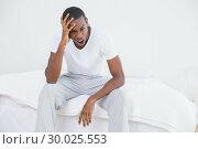 Купить «Afro man yawning in bed at home», фото № 30025553, снято 26 июля 2013 г. (c) Wavebreak Media / Фотобанк Лори