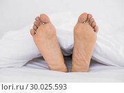 Купить «Close up of bare feet in bed», фото № 30025593, снято 26 июля 2013 г. (c) Wavebreak Media / Фотобанк Лори