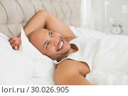 Купить «Smiling young bald man resting in bed», фото № 30026905, снято 1 августа 2013 г. (c) Wavebreak Media / Фотобанк Лори