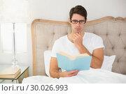 Купить «Relaxed young man reading book in bed», фото № 30026993, снято 2 августа 2013 г. (c) Wavebreak Media / Фотобанк Лори