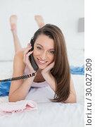 Купить «Portrait of a smiling woman using phone in bed», фото № 30027809, снято 7 августа 2013 г. (c) Wavebreak Media / Фотобанк Лори