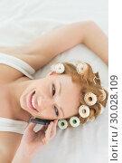 Купить «Relaxed woman in hair curlers using cellphone in bed», фото № 30028109, снято 16 августа 2013 г. (c) Wavebreak Media / Фотобанк Лори