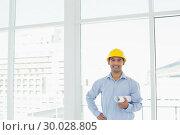 Купить «Young architect in yellow hard hat with blueprint in office», фото № 30028805, снято 8 августа 2013 г. (c) Wavebreak Media / Фотобанк Лори