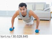 Sporty man with dumbbells doing push ups in the living room. Стоковое фото, агентство Wavebreak Media / Фотобанк Лори