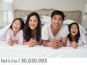Купить «Portrait of a cheerful family of four lying in bed», фото № 30030093, снято 29 августа 2013 г. (c) Wavebreak Media / Фотобанк Лори