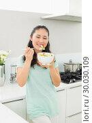 Купить «Smiling young woman with a bowl of salad in kitchen», фото № 30030109, снято 29 августа 2013 г. (c) Wavebreak Media / Фотобанк Лори