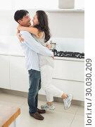 Купить «Side view of a man embracing woman in kitchen», фото № 30030209, снято 29 августа 2013 г. (c) Wavebreak Media / Фотобанк Лори