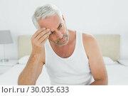 Купить «Thoughtful mature man sitting in bed», фото № 30035633, снято 26 августа 2013 г. (c) Wavebreak Media / Фотобанк Лори