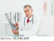 Купить «Confident doctor with xray picture of lungs in office», фото № 30046689, снято 4 октября 2013 г. (c) Wavebreak Media / Фотобанк Лори