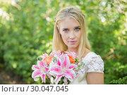 Купить «Blonde bride holding colourful bouquet looking at camera», фото № 30047045, снято 9 октября 2013 г. (c) Wavebreak Media / Фотобанк Лори