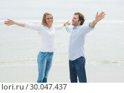 Купить «Happy couple stretching hands out at beach», фото № 30047437, снято 10 октября 2013 г. (c) Wavebreak Media / Фотобанк Лори