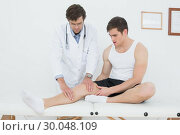 Full length of a young man getting his knee examined. Стоковое фото, агентство Wavebreak Media / Фотобанк Лори