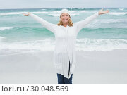 Купить «Casual senior woman with arms outstretched at beach», фото № 30048569, снято 11 октября 2013 г. (c) Wavebreak Media / Фотобанк Лори