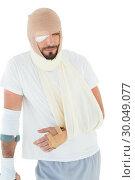 Купить «Man with head tied up in bandage and broken hand», фото № 30049077, снято 16 октября 2013 г. (c) Wavebreak Media / Фотобанк Лори
