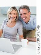 Купить «Happy casual couple using laptop in kitchen», фото № 30049149, снято 17 октября 2013 г. (c) Wavebreak Media / Фотобанк Лори