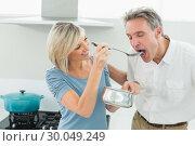 Купить «Loving woman feeding a man in kitchen», фото № 30049249, снято 17 октября 2013 г. (c) Wavebreak Media / Фотобанк Лори