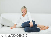 Купить «Portrait of a happy woman on sofa at home», фото № 30049317, снято 17 октября 2013 г. (c) Wavebreak Media / Фотобанк Лори
