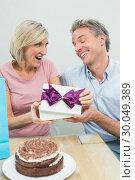 Купить «Man giving a happy woman a birthday gift beside cake», фото № 30049389, снято 17 октября 2013 г. (c) Wavebreak Media / Фотобанк Лори
