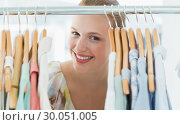 Купить «Happy female customer amid clothes rack», фото № 30051005, снято 5 ноября 2013 г. (c) Wavebreak Media / Фотобанк Лори