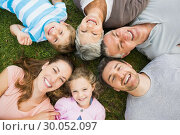 Extended family lying in circle at park. Стоковое фото, агентство Wavebreak Media / Фотобанк Лори