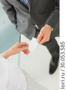 Купить «Businessman handing businesswoman his card», фото № 30053585, снято 3 ноября 2013 г. (c) Wavebreak Media / Фотобанк Лори