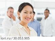 Купить «Happy asian businesswoman standing with team behind her», фото № 30053905, снято 3 ноября 2013 г. (c) Wavebreak Media / Фотобанк Лори