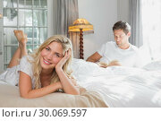 Купить «Relaxed woman with man reading book in background on bed», фото № 30069597, снято 5 декабря 2013 г. (c) Wavebreak Media / Фотобанк Лори